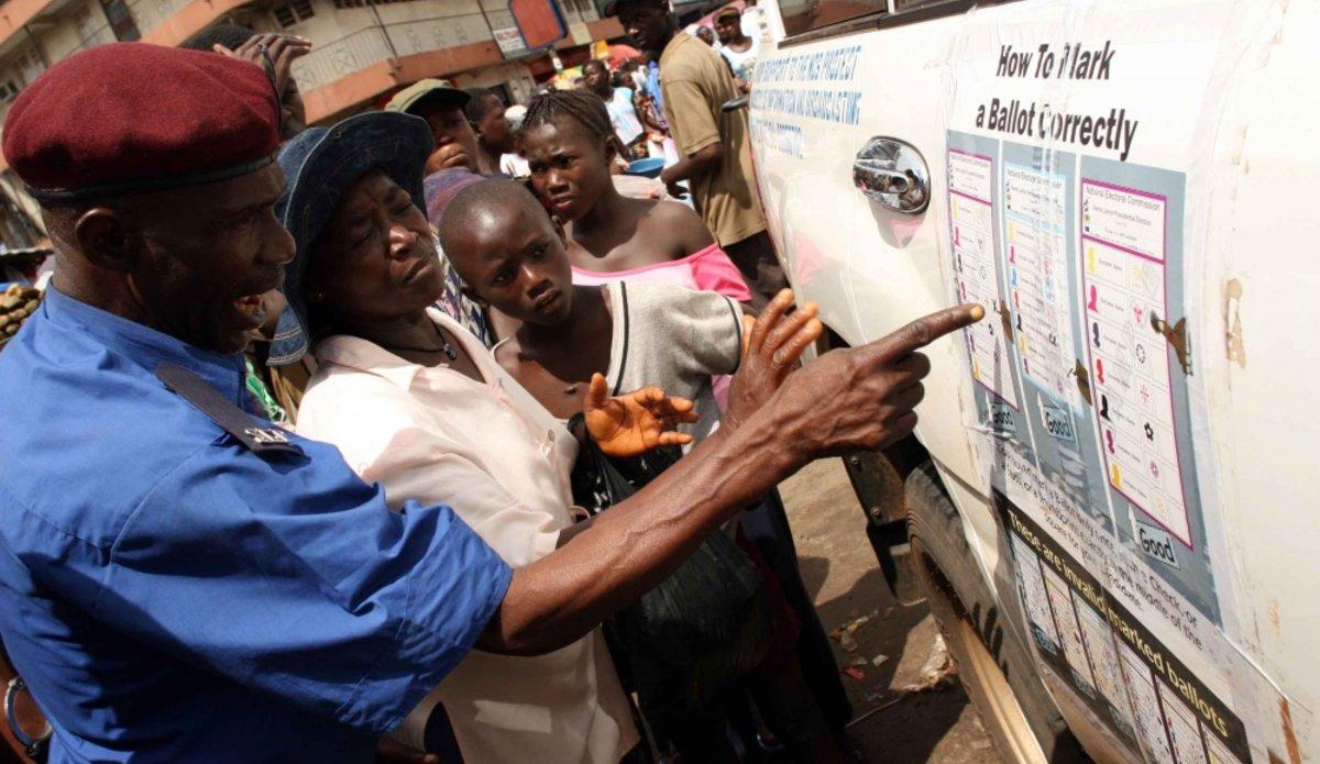 A Freetown, quelques jours avant les élections présidentielles du 11 août 2007, un policier utilise une affiche pour montrer à une femme comment voter correctement. Grace aux forces de sécurité, la Sierra Leone a organisé en 2007 une élection sans violence après 11 années de guerre civile. Crédit : IRIN